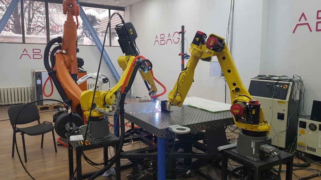 Сварка двух пластин. Один робот поддерживает пластину вертикально, другой делает точный сварочный шов.